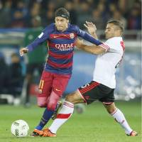 Neymar (left) controls the ball for Barcelona during the Club World Cup final against River Plate on Sunday in Yokohama. | KYODO