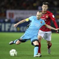 Barcelona's Andres Iniesta (left) controls the ball in front of Guangzhou Evergrande's Huang Bowen on Thursday. | AP