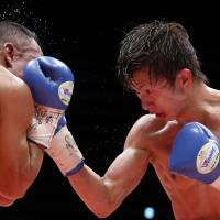 Ryoichi Taguchi (right) punches Luis de la Rosa during their WBA light flyweight title bout on Thursday. | REUTERS