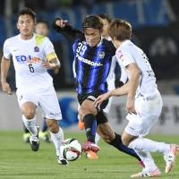 Gamba Osaka's Takashi Usami dribbles past two Sanfrecce Hiroshima defenders during Wednesday's match in Suita, Osaka Prefecture. | KYODO