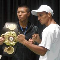 WBA super featherweight champion Takashi Uchiyama (left) and Oliver Flores pose for photos after signing the contract for their title fight on Wednesday at Ota General City Gymnasium. | KAZ NAGATSUKA