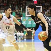 Aisin's Kosuke Kanamaru (right) and Toyota's Keijuro Matsui compete during the NBL Finals in May. Both teams will play in the B. League's top division in 2016. | KAZ NAGATSUKA