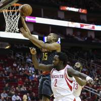 Hawks center Al Horford scores in front of the Rockets' Patrick Beverley (2) and James Harden during their game on Tuesday in Houston. The Hawks erased a 19-point deficit to earn a 121-115 win. | USA TODAY / REUTERS