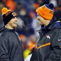 Broncos quarterback Peyton Manning (right) speaks with Bengals signal caller Andy Dalton before Monday's game, which both missed due to injuries. | AP