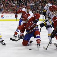The Capitals' Jay Beagle (left) tries to control the puck against the Sabres on Wednesday in Washington.   AP