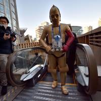 A fan dressed as C-3PO arrives at a Tokyo theater screening Friday for the world premiere of 'Star Wars: The Force Awakens.' | AFP-JIJI