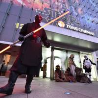 Fans dressed as various 'Star Wars' characters pose in front of a Toho Cinemas in Roppongi to celebrate for the opening of 'Star Wars: The Force Awakens' on Friday. | AFP-JIJI