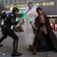 Men wielding lightsabers strike a pose with a woman dressed as Padme Amidala in front of Toho Cinemas' Roppongi Hills theater in Tokyo's Minato Ward on Friday ahead of the premiere of 'Star Wars: The Force Awakens.' | RIE ISHII