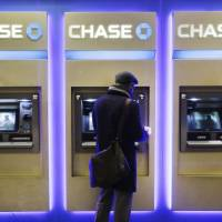 A customer uses an ATM at a branch of Chase Bank on Jan. 14 in New York. JPMorgan Chase will roll out later in 2016 new ATMs that will allow customers to access the machine or withdraw cash using their cellphone, the company said Monday. | AP