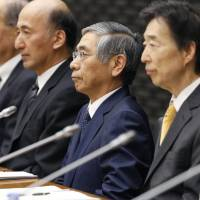 Bank of Japan Gov. Haruhiko Kuroda (center) attends the central bank's quarterly meeting with branch managers at the BOJ headquarters in Tokyo on Monday. | KYODO