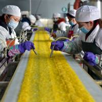 Employees work at a Chinese food processing factory in Yichang, Hubei province, on Sunday. | REUTERS