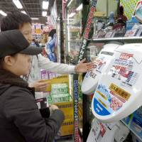 A sales person explains toilet seat options at an electronics store in Tokyo. Chinese tourist spending may suffer as the yuan weakens against the yen. | KYODO