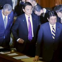 Finance Minister Taro Aso (center) prepares to leave the Lower House with Prime Minister Shinzo Abe and economics minister Akira Amari (front left) at the Diet on Monday. | REUTERS