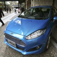 A man looks at a Ford Fiesta compact in Tokyo on Jan. 9. Ford Motor Co. said Monday that it's pulling out of Japan and Indonesia before the end of the year because there is no path to grow sales or make sustained profits. | AP