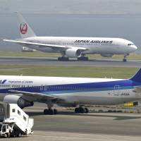 Planes pass at Haneda airport. Domestic carriers are set to remove fuel surcharges as oil prices have plunged to their lowest levels in years. | BLOOMBERG
