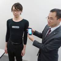 A man models an electrically conductive garment that transmits data to a user's cellphone. It was developed by underwear-maker Gunze Ltd. and electronics giant NEC Corp. | KYODO