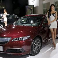 A model poses next to an Acura TLX car during the Imported Auto Expo in Beijing last September.  Honda Motor Co. will launch a new small crossover sport utility vehicle in China later this year. | REUTERS