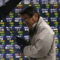 A pedestrian walks past an electronic board showing stock prices outside a brokerage in Tokyo on Monday. | REUTERS
