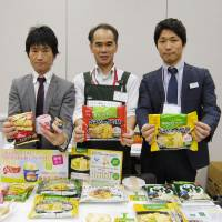 Ezaki Glico Co. employees show off frozen noodles, ice cream and other foods with low carbohydrate content in Tokyo in November. | KYODO
