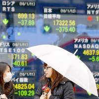 Women chat in front of an electronic stock indicator at a securities firm in Tokyo on Tuesday. | AP
