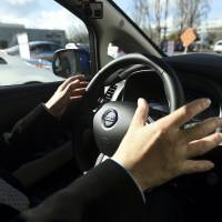 Nissan Motor Co. General Manager Tetsuya Iijima demonstrates an autonomous drive Nissan Leaf during a preview of autonomous Renault-Nissan Alliance vehicles in Sunnyvale, California, Thursday. | REUTERS