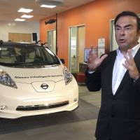 Carlos Ghosn, chairman and CEO of Nissan, speaks next to a prototype of the autonomous driving Nissan Leaf at Renault-Nissan Silicon Valley in Sunnyvale, California, Thursday. The Renault-Nissan Alliance is entering the race to build autonomous cars with a plan to introduce 10 models capable of temporarily relieving humans of their driving duties on highways and city streets. | AP
