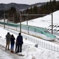 People watch a Hokkaido Shinkansen bullet train during its test run Jan. 1 in the town of Kikonai, Hokkaido, ahead of its official launch scheduled for March 26. | KYODO