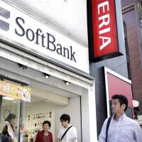 Pedestrians walk past the entrance to a SoftBank store in Tokyo in September. | BLOOMBERG