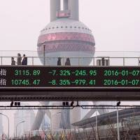 People walk along a pedestrian bridge with a screen showing stock market movements in Shanghai on Thursday. China's market regulator extended restrictions on big shareholders selling stocks, on whom a ban had been due to expire at the end of the week, as trade was suspended in the morning following a 7 percent plunge. | AFP-JIJI