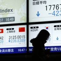 A pedestrian walks past an electronic stock board displaying the Nikkei 225 stock average (top right) and the Shanghai Stock Exchange Composite Index (second from bottom left) outside a securities firm in Tokyo on Thursday. | BLOOMBERG