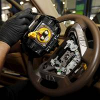 A technician holds a Takata air bag inflator after removing it from a Honda Pilot SUV  in June. | REUTERS