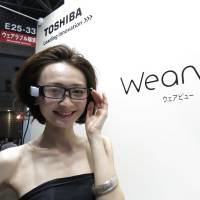 A model wears Toshiba Corp.'s glasses device Wearvue at the Wearable Expo at Tokyo Big Sight on Wednesday.   KAZUAKI NAGATA