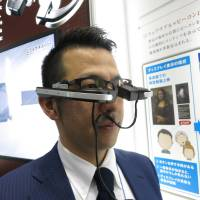 A Meganesuper employee tries on its wearable device called b.g. The b.g. projectors are attached to the temples of the glasses. | KAZUAKI NAGATA