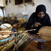 Music maker: Cheynoune Zeineb, a Tuareg and imzad instrument maker, decorates an imzad with personalized Tuareg motifs in Tamanrasset, southern Algeria, earlier this month. | AFP-JIJI