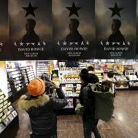 Posthumous hit: A  fan takes a photo of posters depicting British rock star David Bowie's last album, 'Blackstar,' displayed at a music retailer in Tokyo last week. | REUTERS