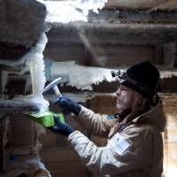 Mawson's Huts Foundation chief conservator Ian Godfrey chips ice from shelves in Douglas Mawson's bedroom in Mawson's Huts at Cape Denison in Antarctica last month. | REUTERS