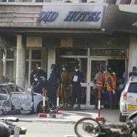 Rescue workers carry a body from the Splendid Hotel in Ouagadougou on Saturday after Burkina Faso and French security forces killed four jihadi attackers and freed more than 126 people. | AP