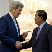 U.S. Secretary of State John Kerry greets Cambodian Prime Minister Hun Sen at the Peace Palace in Phnom Penh on Tuesday. | REUTERS
