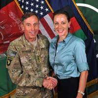 Gen. Davis Petraeus shakes hands with Paula Broadwell, co-author of  'All In: The Education of General David Petraeus,' on July 13, 2011. | AP