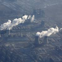 Chimneys from a power plant emitting smog are pictured from a plane on the outskirts of Beijing on Friday. | REUTERS