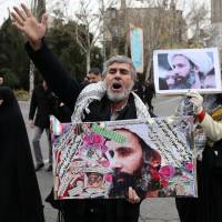 An Iranian worshipper holds a poster showing Sheikh Nimr al-Nimr, a prominent opposition Saudi Shiite cleric who was executed by Saudi Arabia, as he chants slogans while attending an anti-Saudi protest rally after Friday prayers in Tehran. | AP