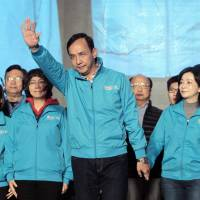 Taiwan's ruling KMT or Nationalist Party presidential candidate Eric Chu (center) waves to supporters as he concedes defeat in the presidential election in Taipei on Saturday. | AP