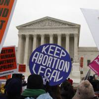 Pro-abortion rights signs are seen Friday during the March for Life 2016, in front of the U.S. Supreme Court in Washington. The Supreme Court will not allow North Dakota to enforce a law banning abortions when a fetal heartbeat is detected as early as six weeks into a pregnancy. The justices on Monday turned away the state's appeal of lower court rulings that struck down the 2013 fetal heartbeat law as unconstitutional. | AP