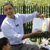 President Barack Obama, accompanied by first lady Michelle Obama and daughter Malia, reads 'Green Eggs and Ham' at the annual White House Easter Egg Roll on April 5, 2010. | AP