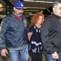 Tonya Couch is taken by authorities to a waiting car after arriving at Los Angeles International Airport, Thursday.   AP