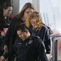 Tonya Couch is escorted off a flight after her arrival to the Dallas/Fort Worth International Airport in Grapevine, Texas, Thursday. Couch, mother of a fugitive teenager known for using an 'affluenza' defense in a deadly drunken-driving case, waived extradition and was sent to Texas from California to face a charge of hindering the apprehension of a felon. | AP