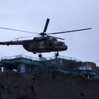 An Afghan National Army helicopter drops commandos on the roof of a building during an operation near the Indian Consulate in Mazar-i-Sharif, Afghanistan, Monday. Afghan special forces prepared to clear insurgents barricaded in a house near the consulate after an overnight attack that coincided with an assault on an Indian airbase near the border with Pakistan. | REUTERS
