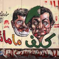 Graffiti depicting Egyptian President .Mohammed Morsi (left), ousted president Hosni Mubarak (right) and former army chief Field Marshal Mohammed Hussein Tantawi cover the walls outside the presidential palace in Cairo in December 2012. | AFP-JIJI
