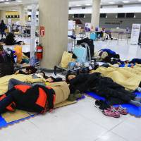 Stranded travellers sleep at Jeju Airport on Monday. Close to 90,000 people were stranded on the South Korean resort island of Jeju after the biggest snowfall in three decades shut the airport for the third straight day.  | AFP-JIJI