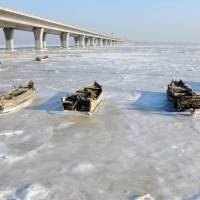Row boats sit stuck in the ice of the frozen coastal waters of Jiaozhou Bay in Qingdao in eastern China's Shandong Province on Monday. Snow, sleet and icy winds across Asia caused deaths, flight cancellations and chaos over the weekend as areas used to basking in balmier climates struggled with record-low temperatures.  | AFP-JIJI